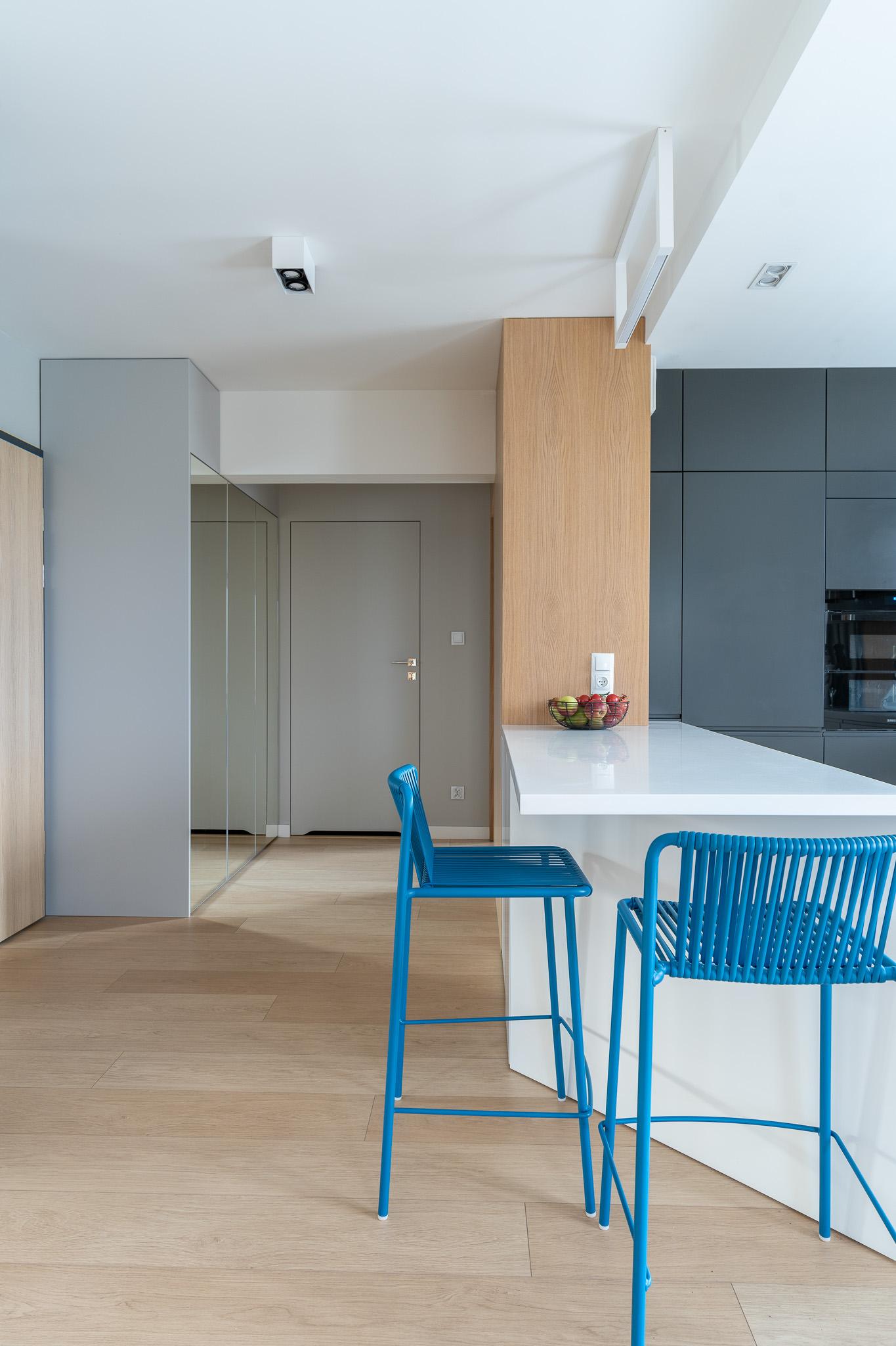 6 projketowanie wnetrz R105 mieszkanie Krakow strefa wejsciowa szafa z lustrami drewno na scienie biala polwyspa z hokerami