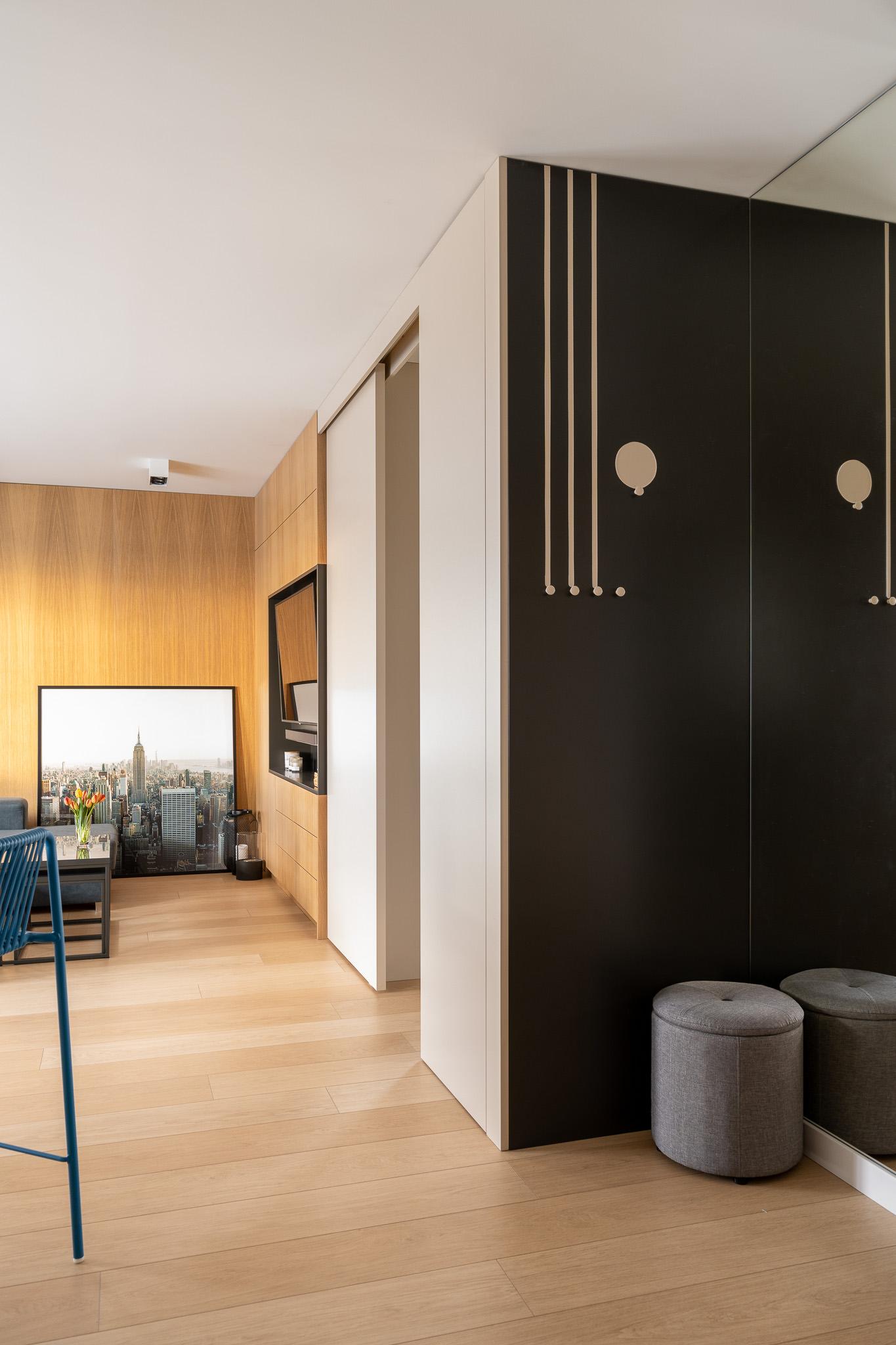 8 projketowanie wnetrz R105 mieszkanie Krakow strefa wejsciowa wieszaki na scianie lustro klejone do sciany szara pufa jasne panele